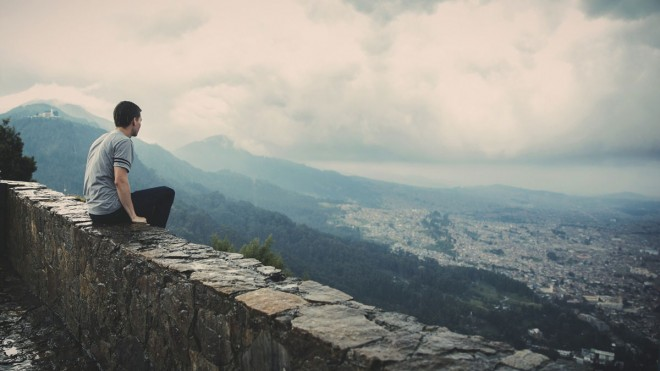 Man-on-the-couch-unsplash, man sitting on stone wall looking at city and mountains