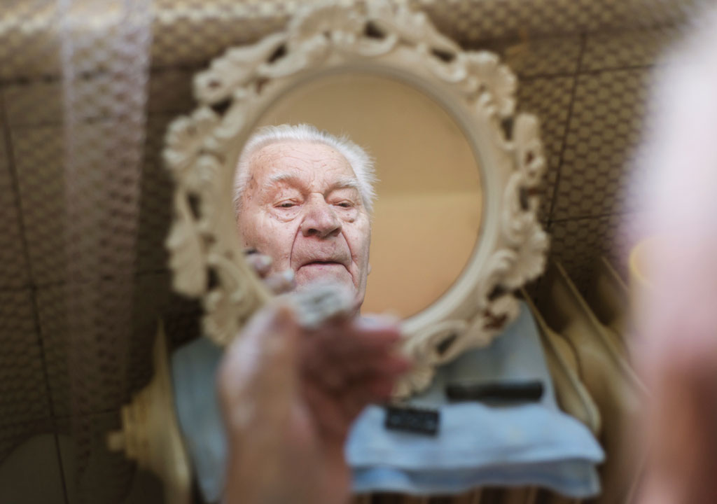 Old man looking in mirror