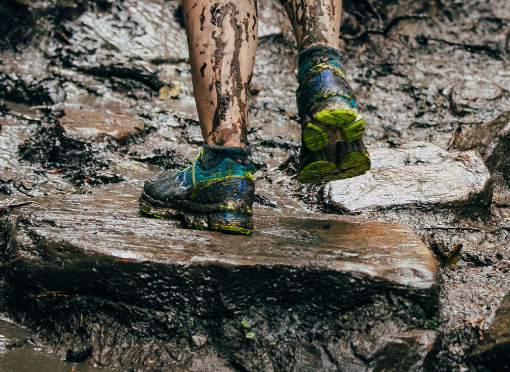 Hiker stepping on rock with muddy shoes