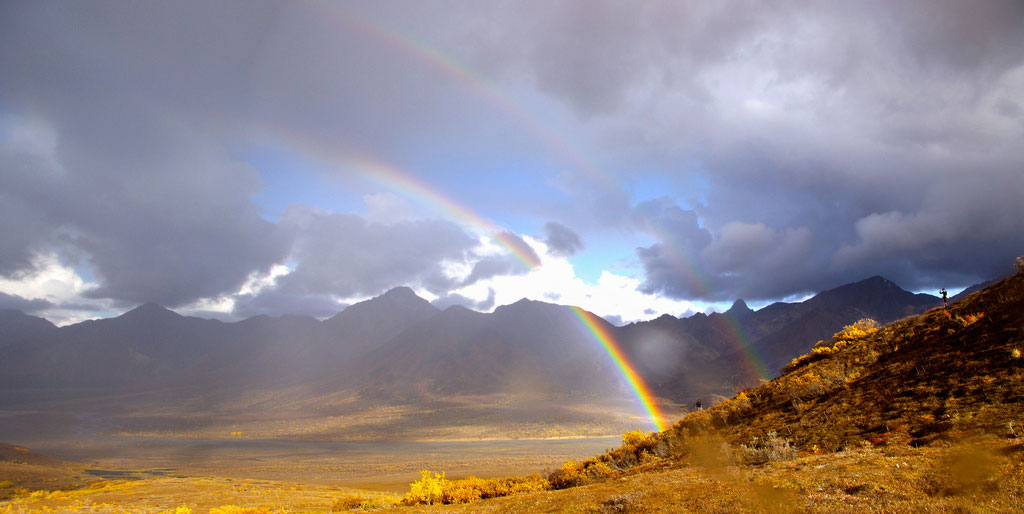 Mountains and fields with rainbow cutting through clouds