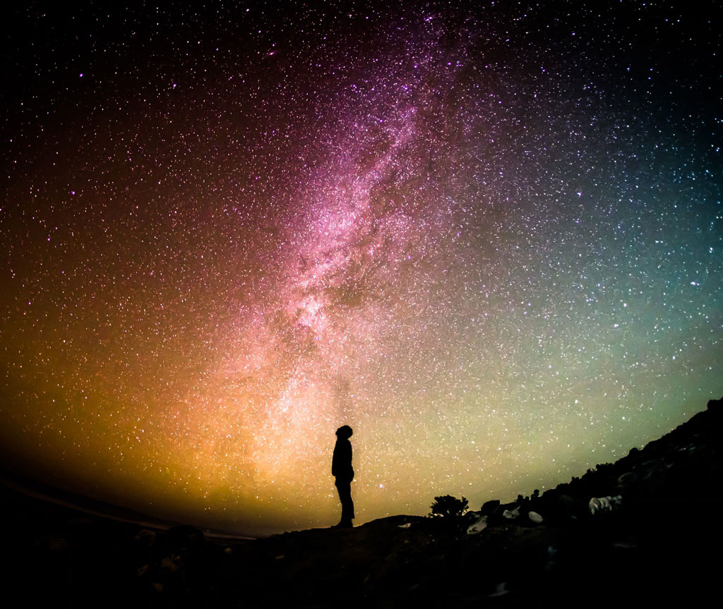 Man staring at colorful milky way