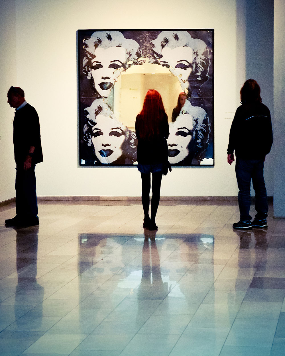 People standing in a museum looking at a painting