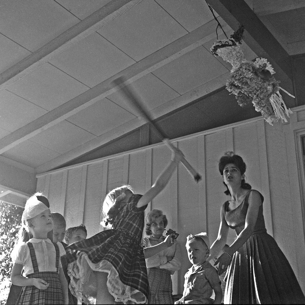 Children knocking down pinata at party