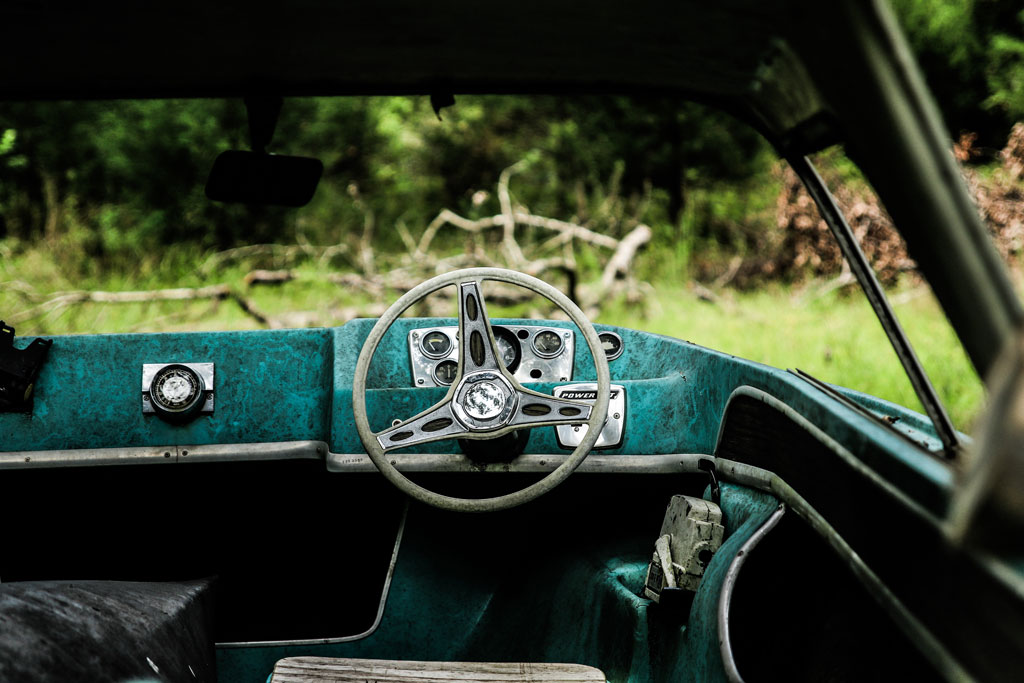 Abandoned car with steering wheel and green interior