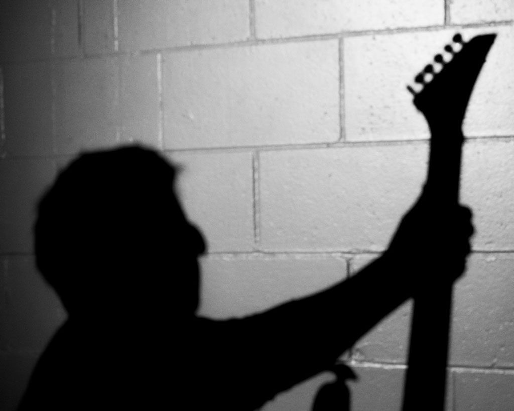 Silhouette of someone holding up an electric guitar