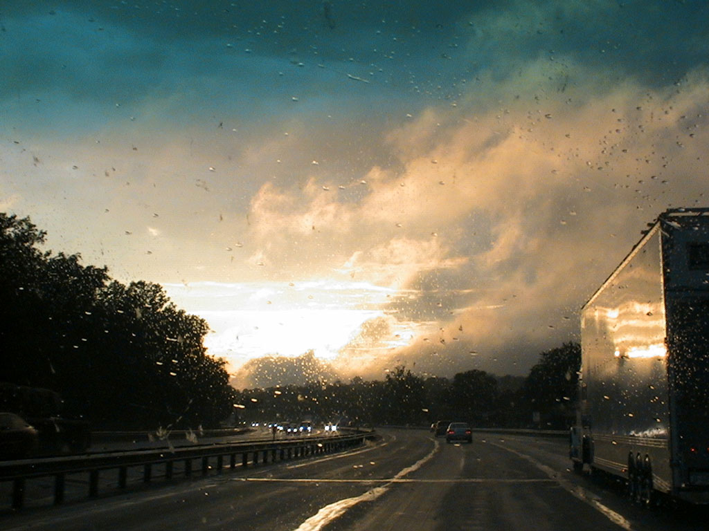 A highway during sunset on a rainy day