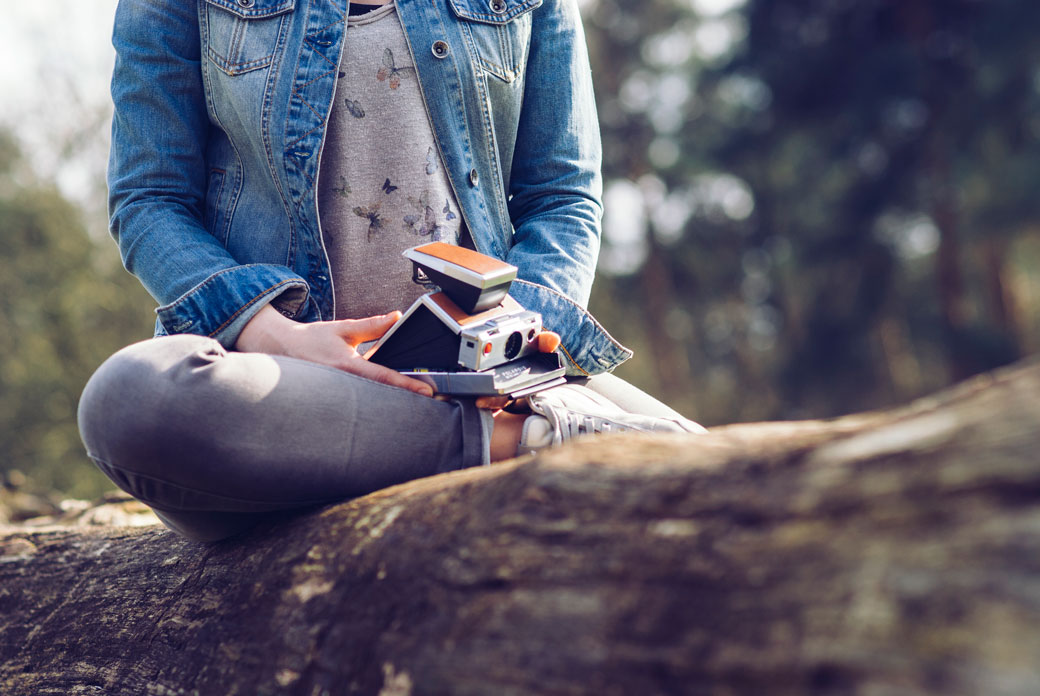 Emotion-is-not-plot, woman holding polaroid camera sitting on log in forest