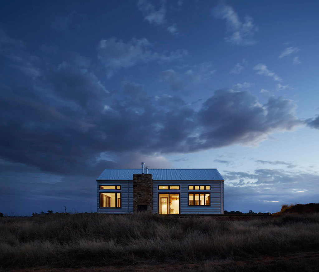 Small white house with large windows in a grassy field at night