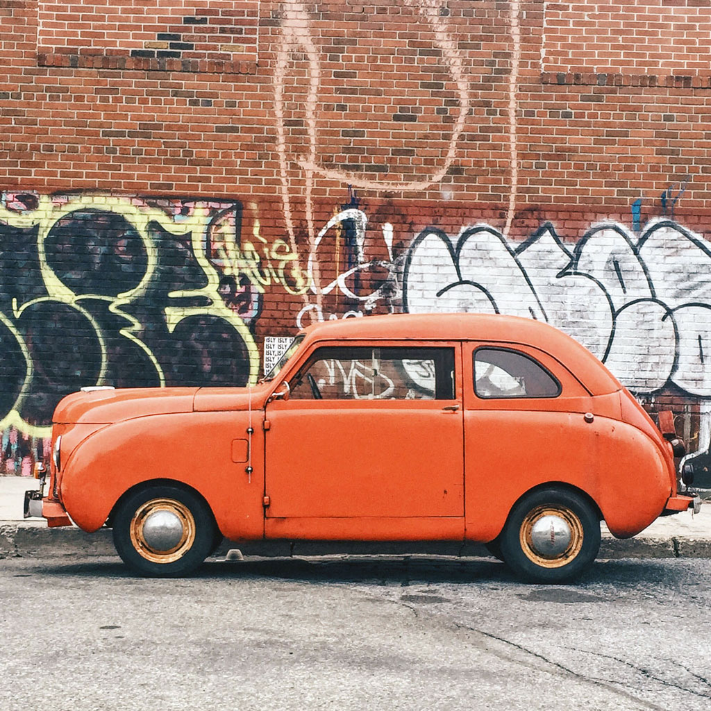 Orange car in front of graffiti