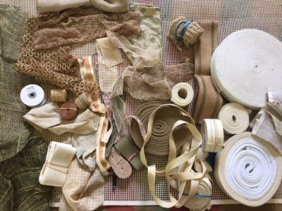 Flat-lay photo of white, brown, and cream-colored crafting supplies including fabric and ribbon
