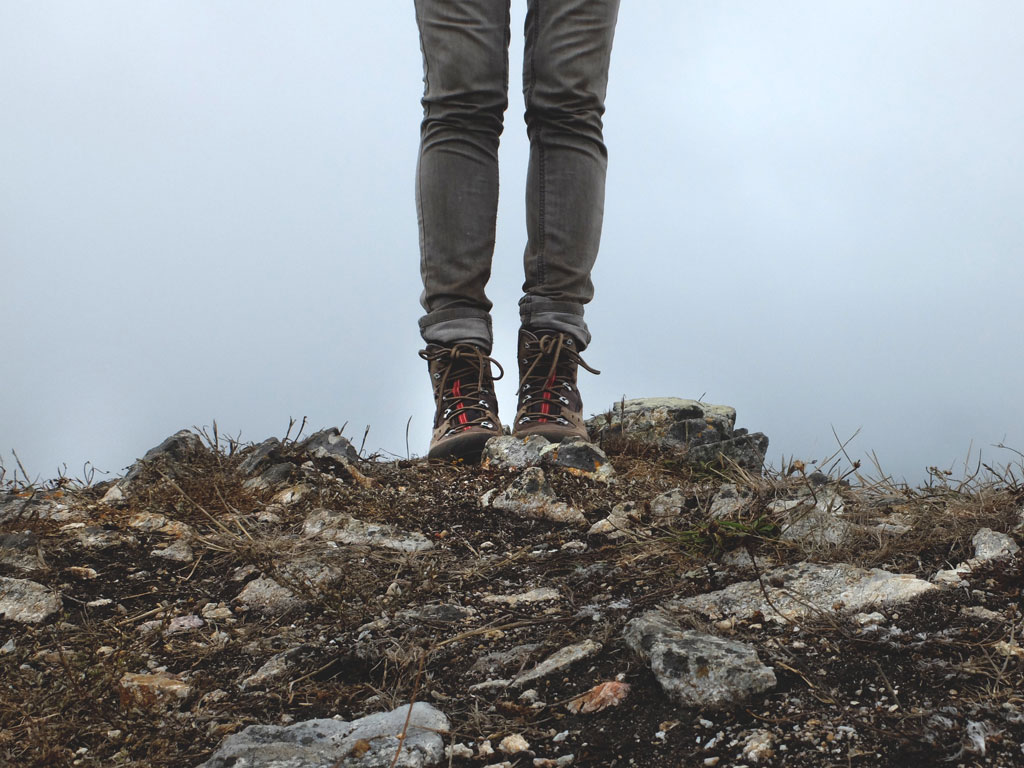 Two legs in hiking boots standing on rocky soil