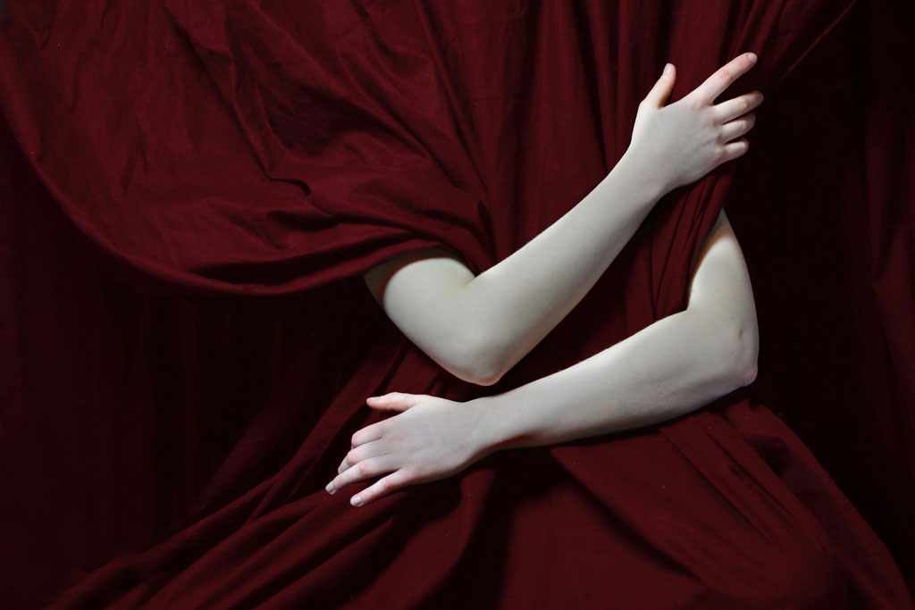 Pale arms around red curtain