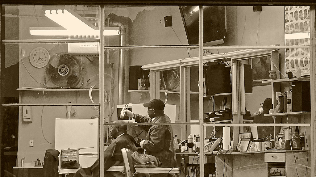 Barber shaving man's hair in barbershop