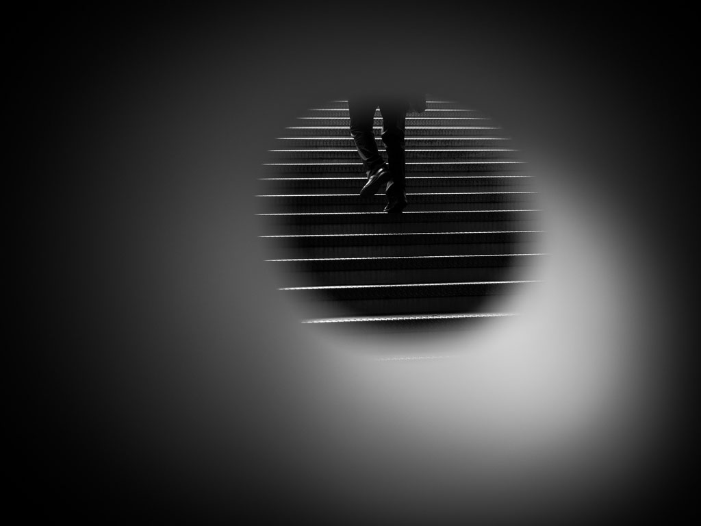 Person walking up a flight of stairs, viewed through a small circle lense