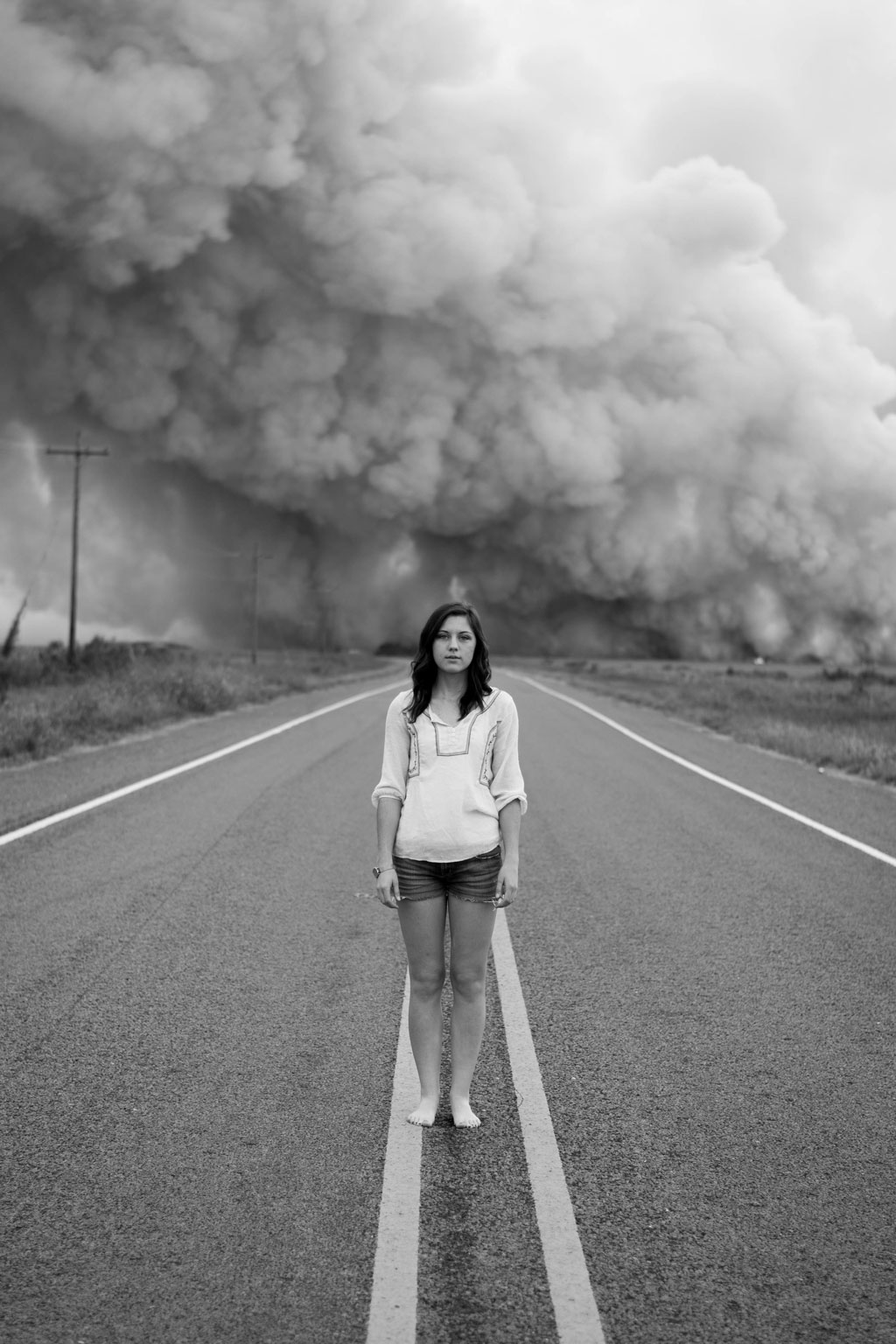 black and white photo of woman standing on road's divider with dust clouds in background