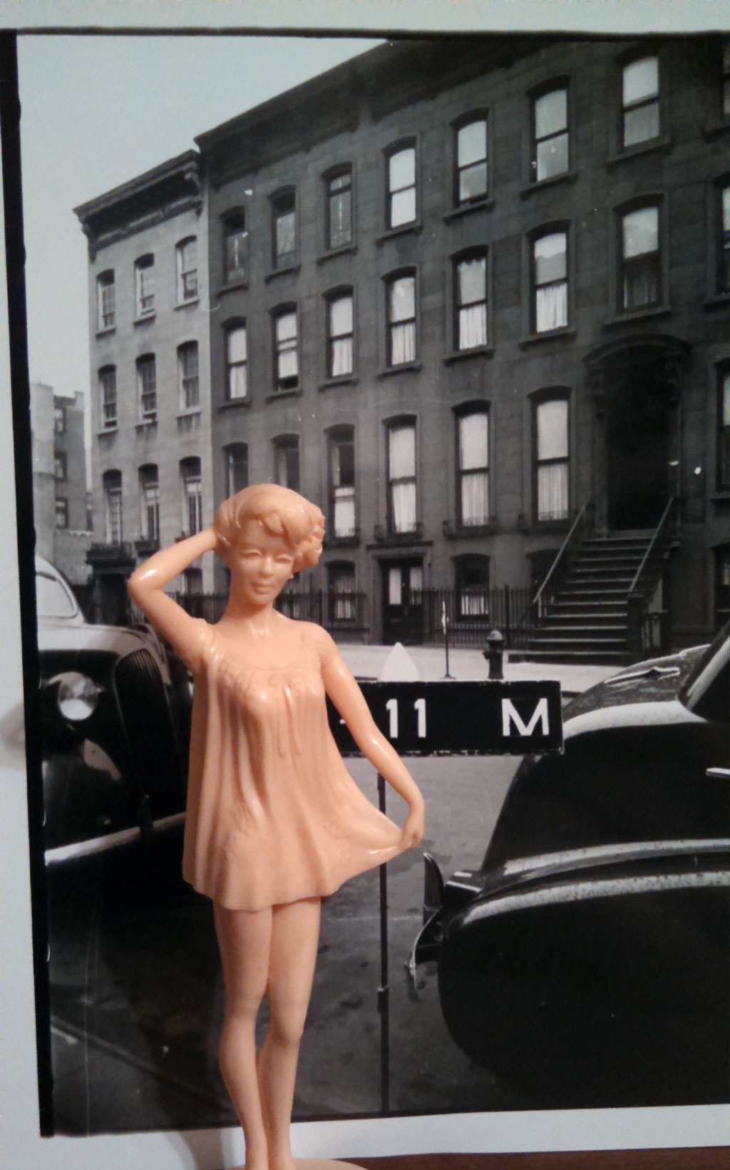 doll in front of black and white photo of residential building