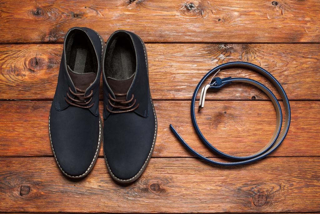 Black Chelsea boots and black belt on rustic wooden floor