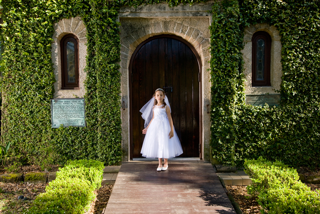 Girl in communion dress in front of ivy-covered bricks