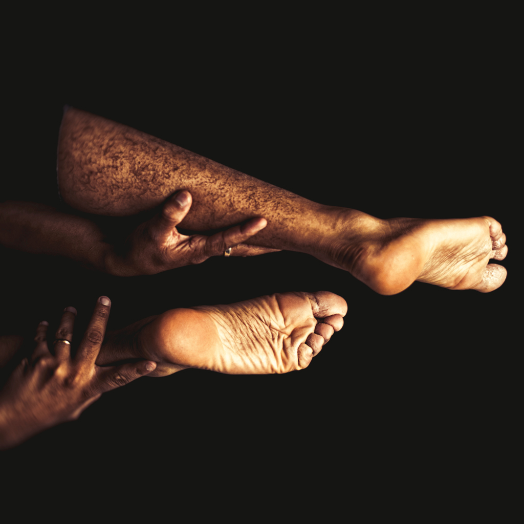 Two legs in the air, with the soles of their feet showing, with hands holding the legs up