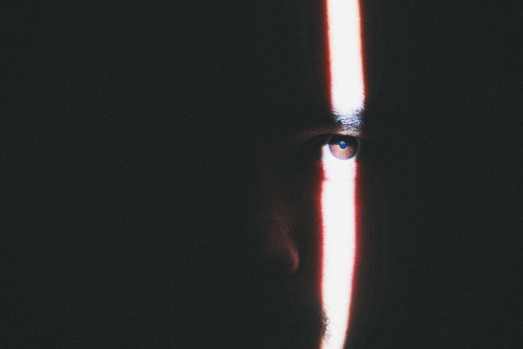 Person in a dark room with a streak of light over their eye