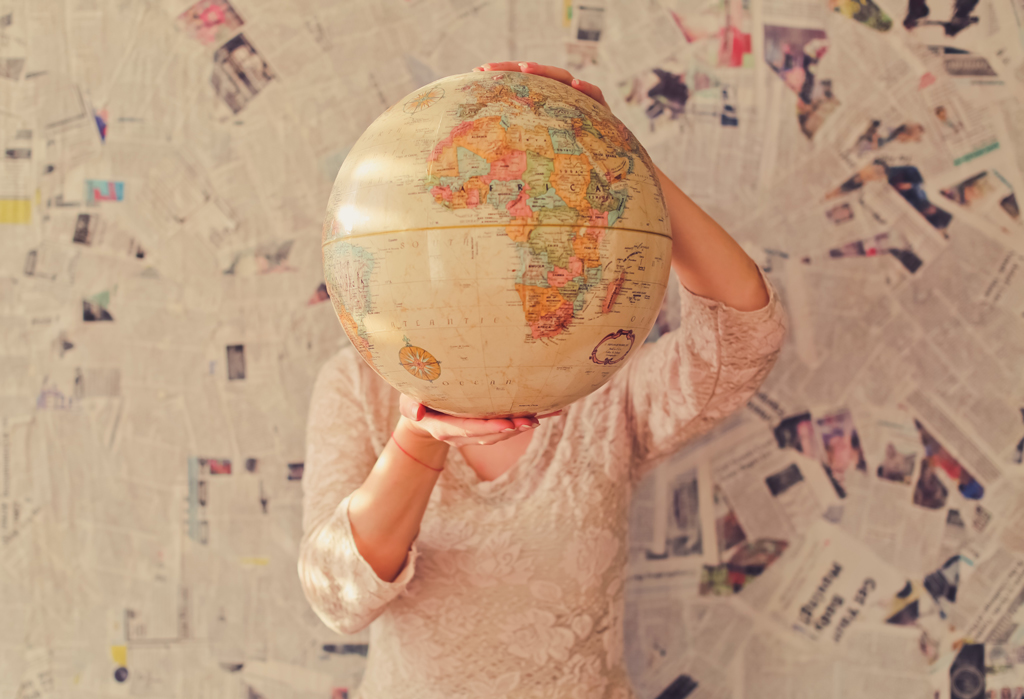 Person holding a globe in front of their head, against a wall covered in newspaper clippings