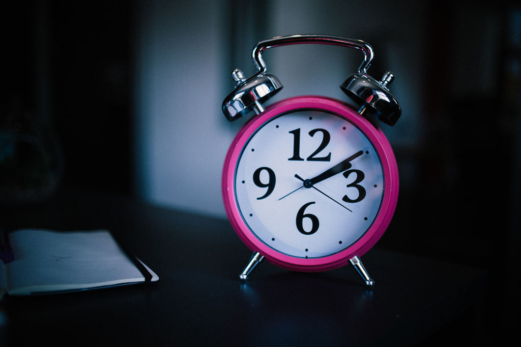 pink alarm clock against dark, fade-out background