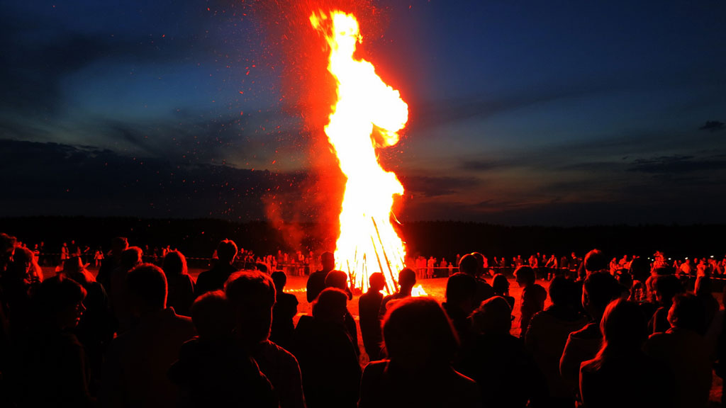 Hundreds of people sitting around a giant bonfire at night