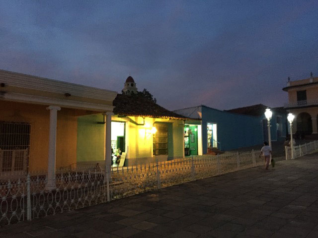 lit-up building in row of colorful buildings against dark sky