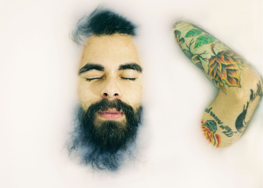 Bearded man submerged in a milk bath, with his face and left arm that's covered in nature-themed tattoos emerging from the bath