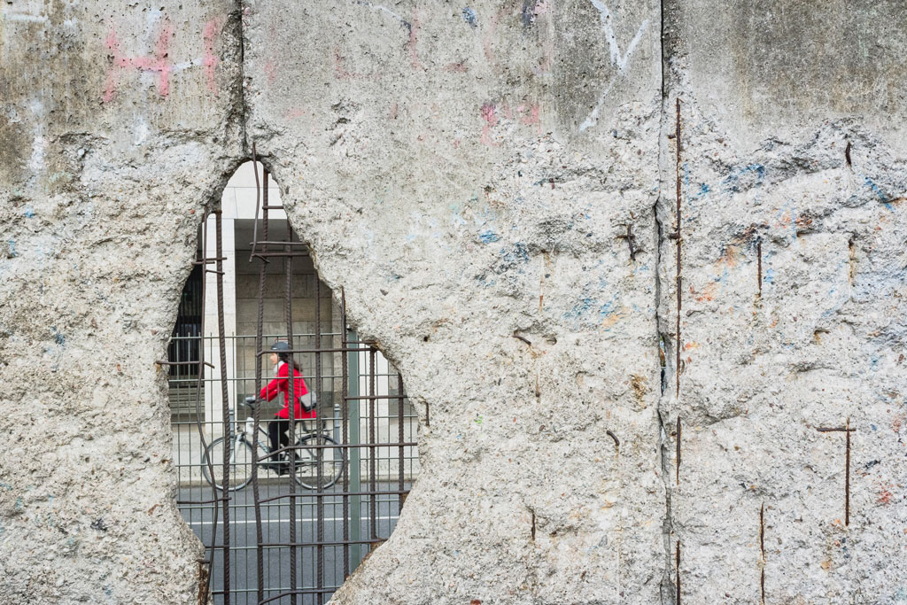 Girl riding a bicycle while wearing a red sweater, seen through a hole in a concrete wall