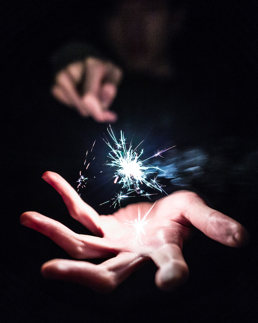 Two hands holding a sparkler in the dark