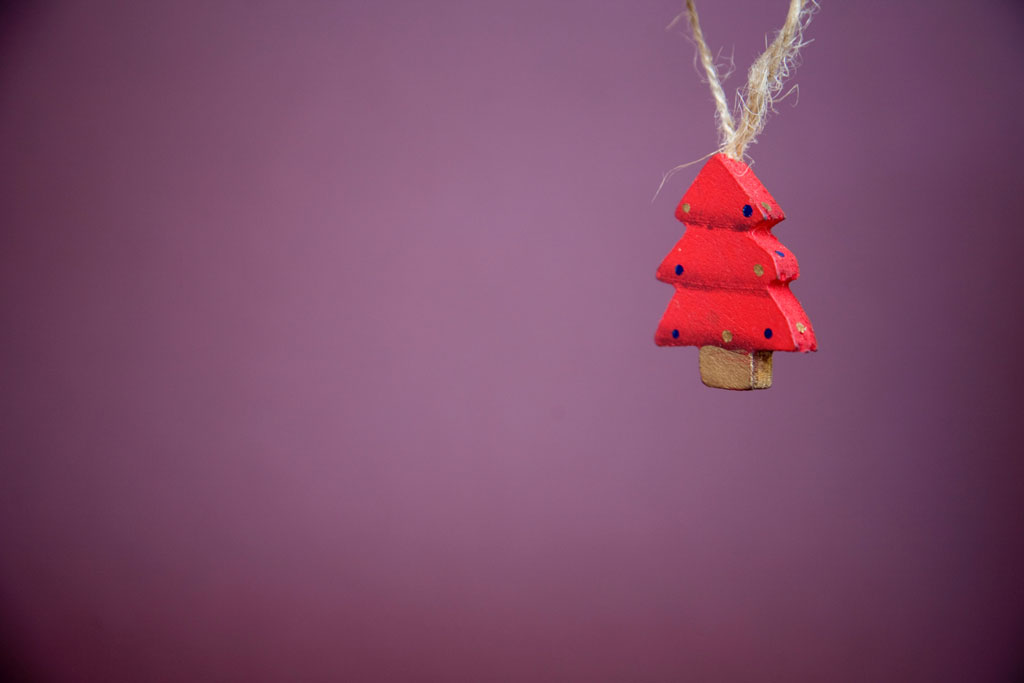 Red Christmas tree ornament hanging by yarn in front of a purple background