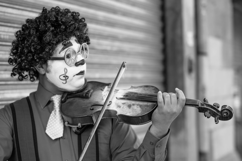 Clown wearing full makeup, a curly wig, and peace sign glasses playing a dusty violin