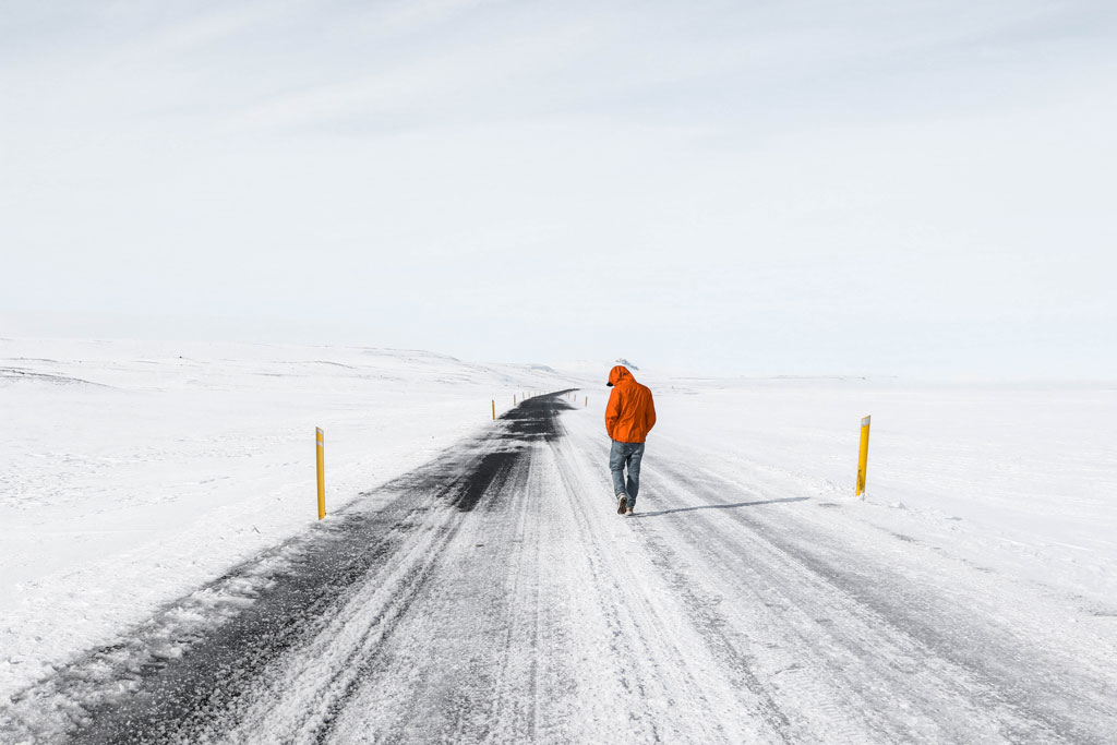 Person wearing an orange winter coat walking on an icy road surrounded by snow