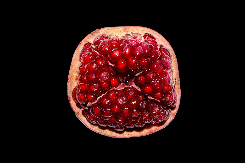 Half of a pomegranate against a black background