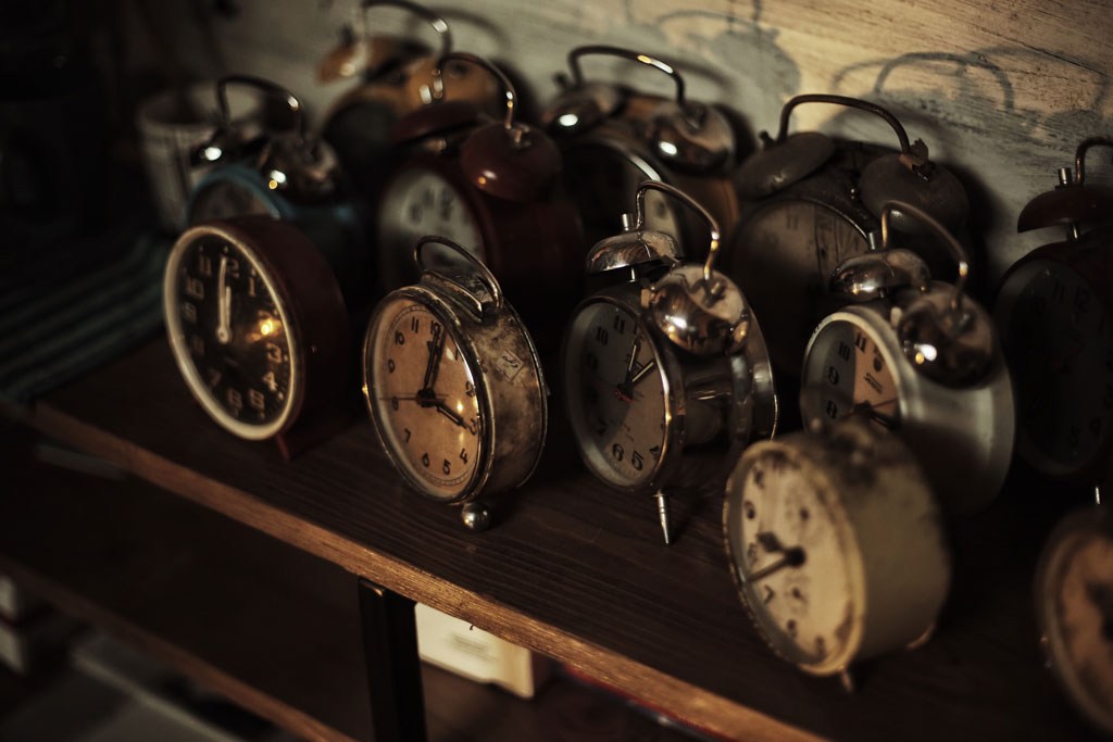 Twelve rusty alarm clocks on a wooden shelf