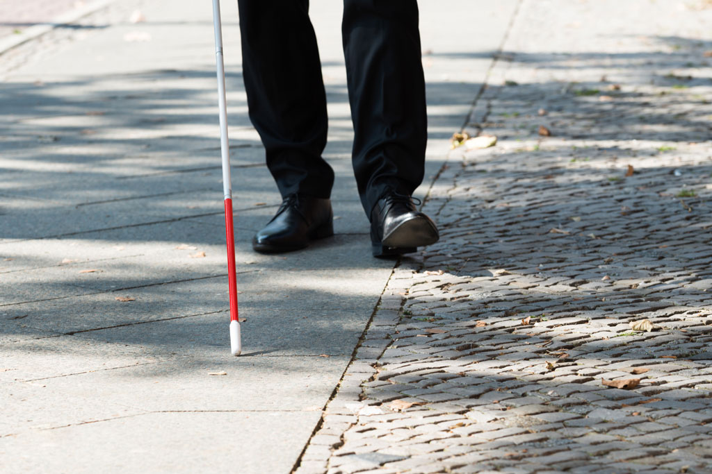 Person holding a walking stick against the sidewalk