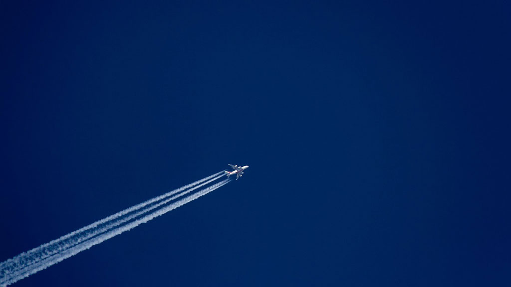 Airplane flying across blue sky with flight lines
