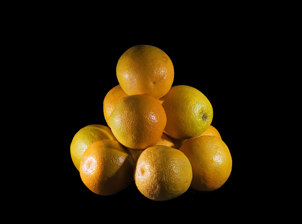 Oranges stacked on top of each other against a black background