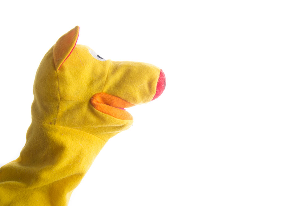 Yellow sock puppet against white background