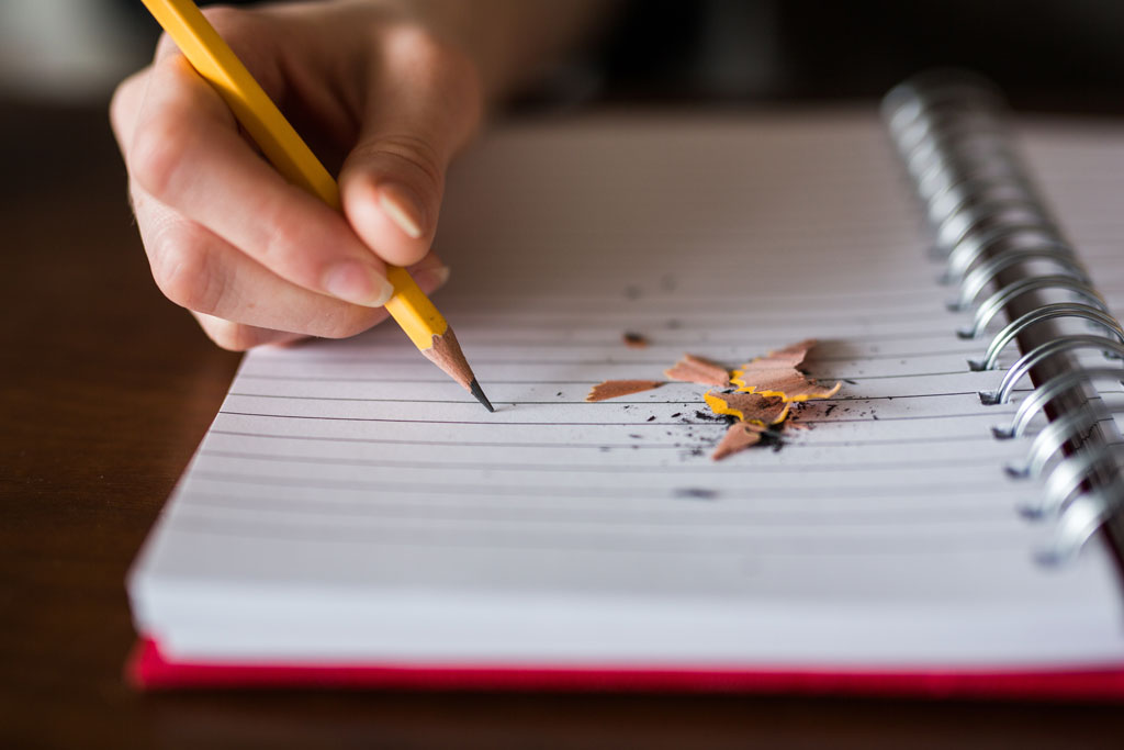 hand holding pencil over open notebook with pencil shavings on it