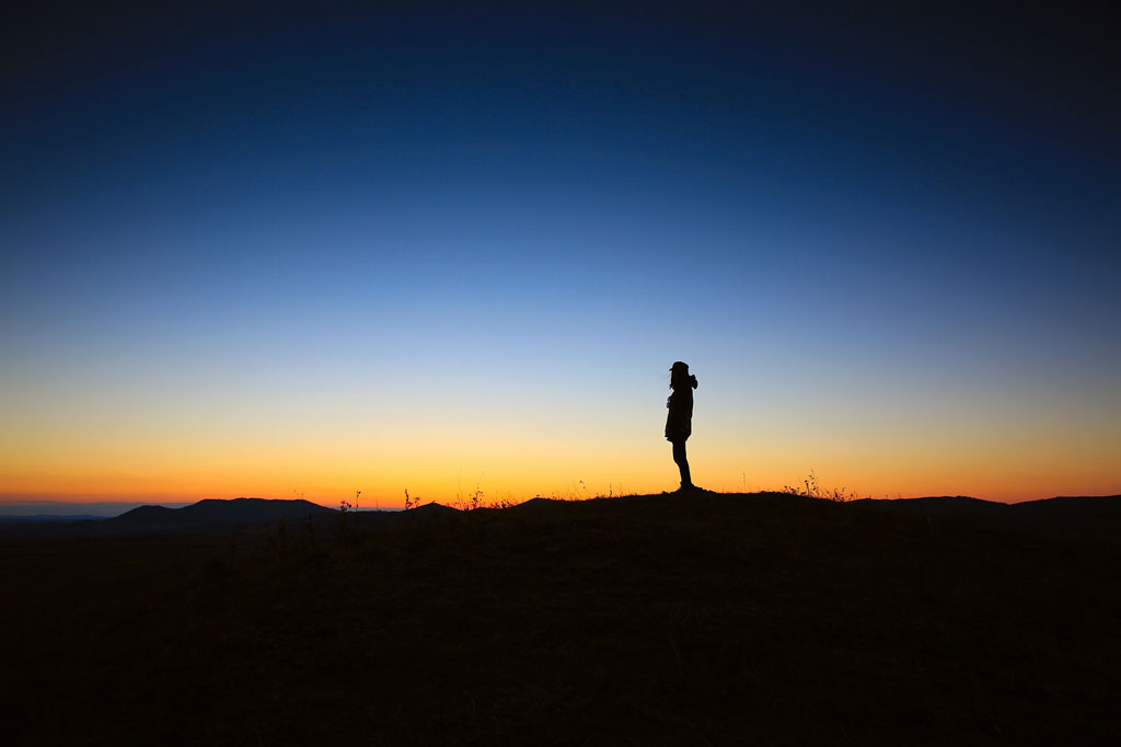 Silhouette of a man watching the sunset over the mountains