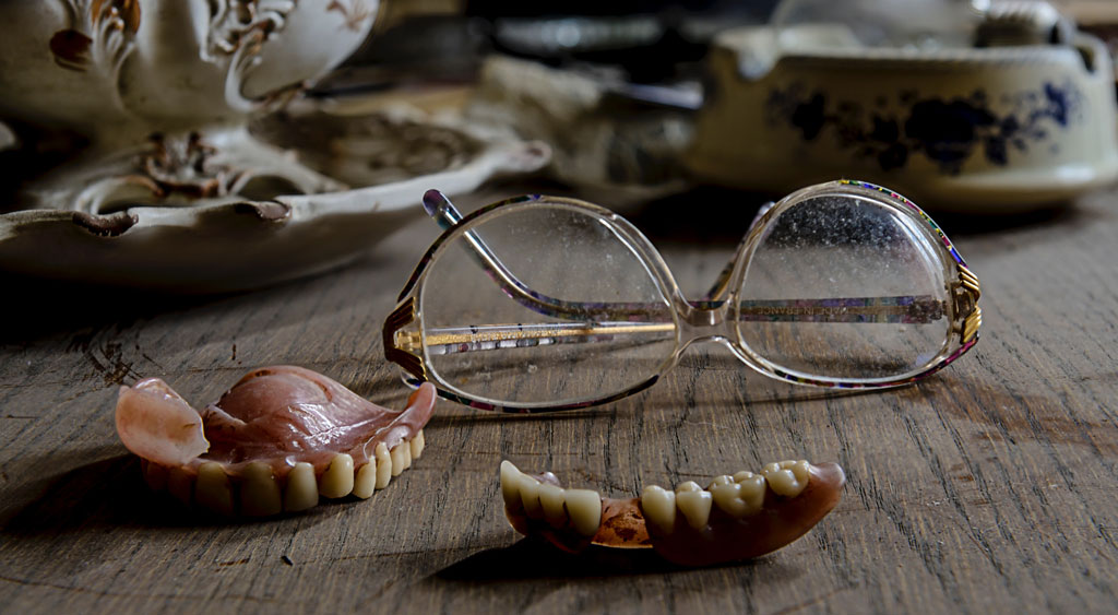Reading glasses, dentures, and old china plates laying on a wooden surface