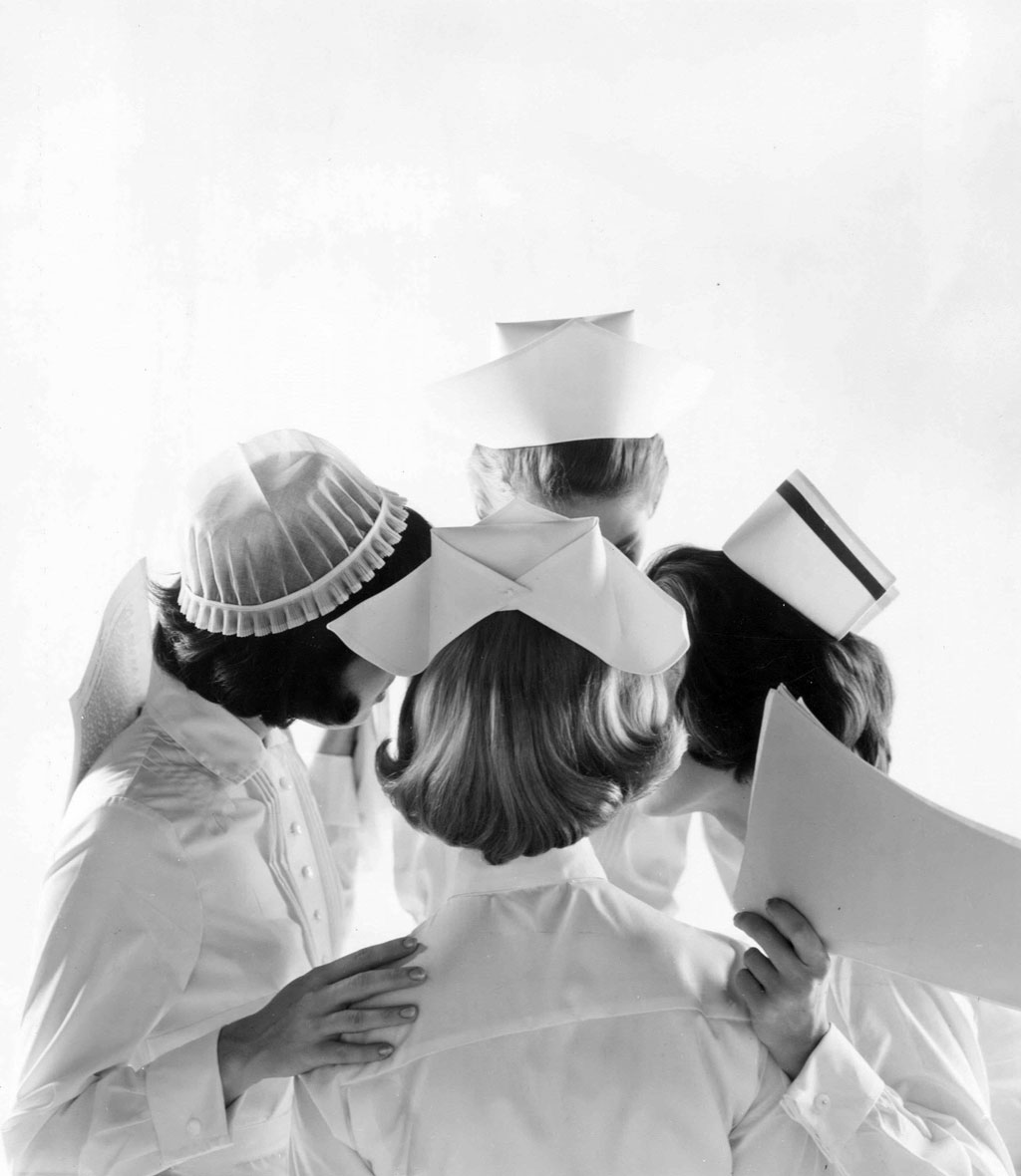 Four nurses in vintage linen hospital attire huddled in a circle
