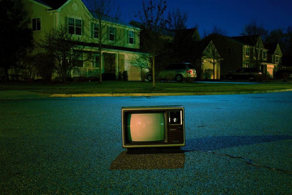 Dark suburban street with blank tv on road