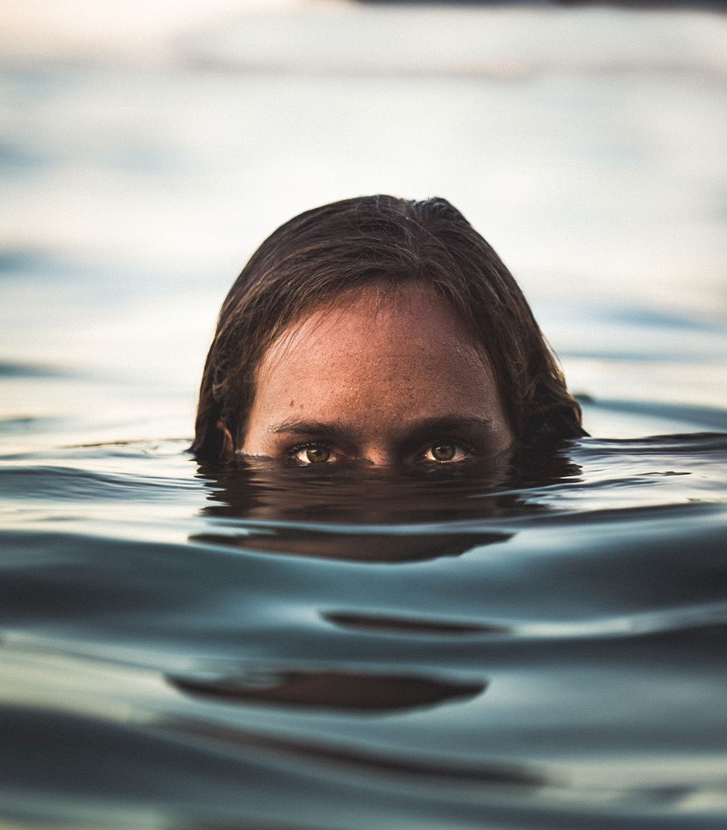 Person's face half-submerged in a pool of water