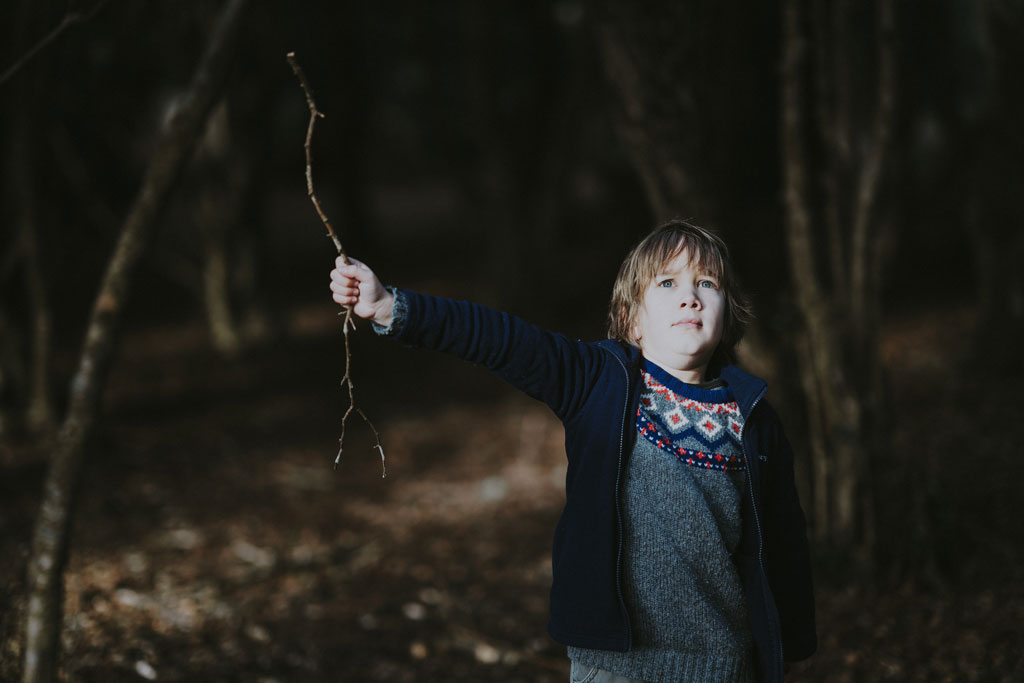 Child holding a tree branch in a dark forest and looking ahead with a scared expression