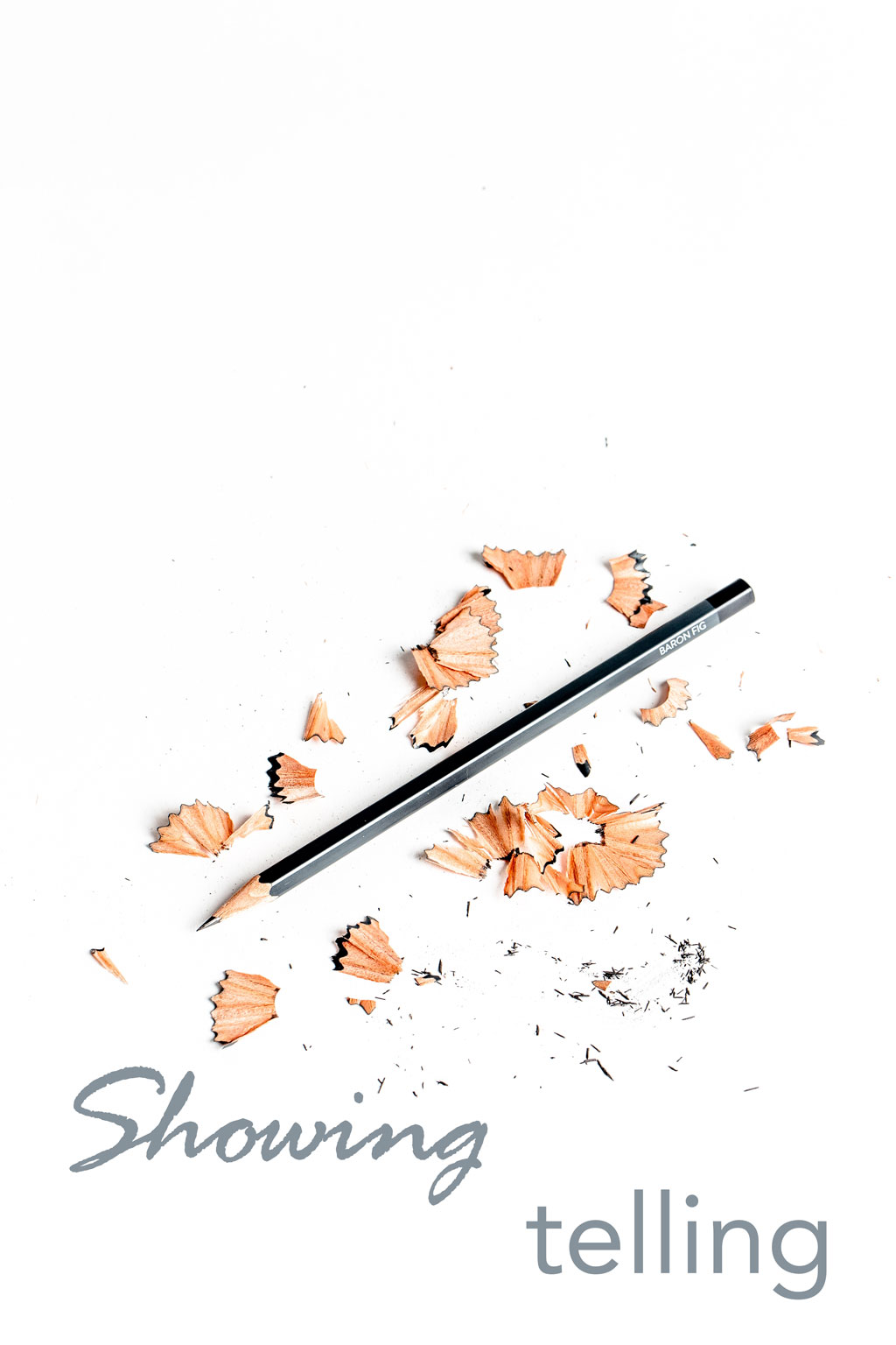 sharpened pencil lying amidst pencil shavings and text saying 'showing' and 'telling' on white background