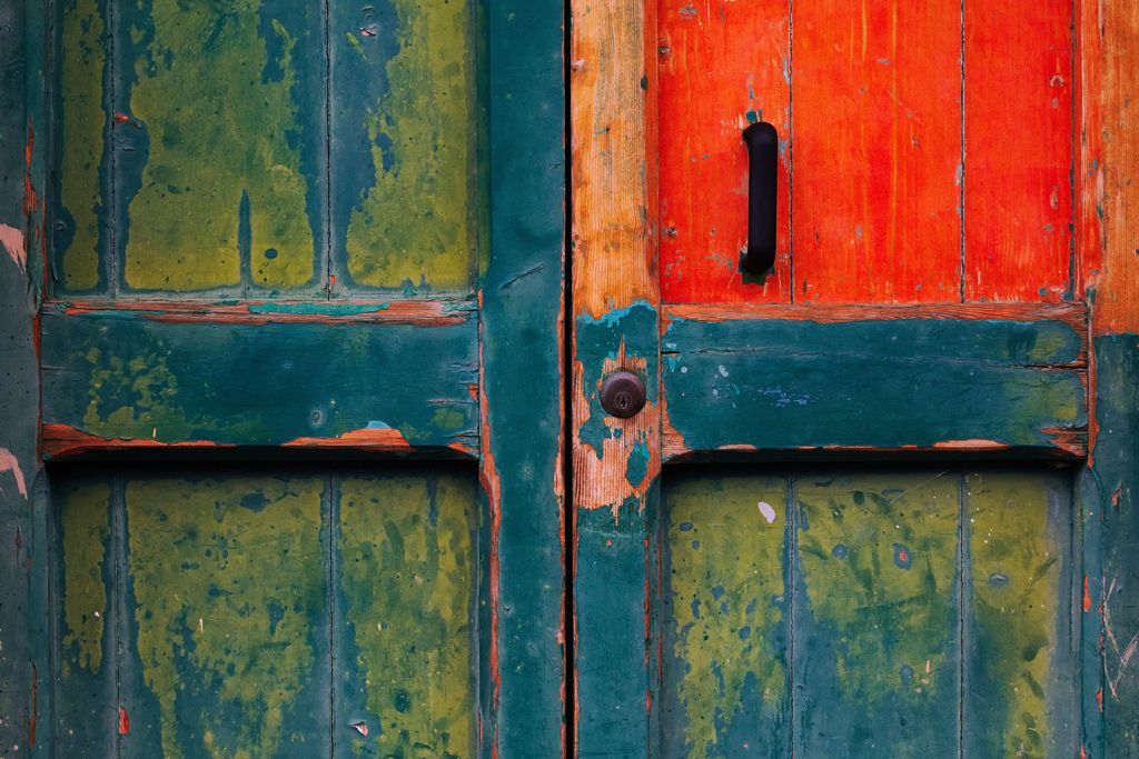 Colored door with splotches of blue, green, and orange paint