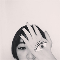 Gloria Yuen with an eye painted on one of her hands that covers her eye